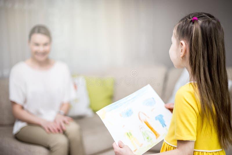 De kinddochter wenst mamma geluk en geeft haar die schilderen En Mum en meisje die glimlachen koesteren Familievakantie en geluk royalty-vrije stock foto's
