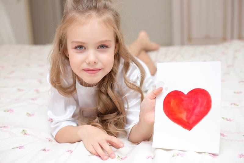 De kinddochter wenst mamma geluk en geeft haar een prentbriefkaar stock foto