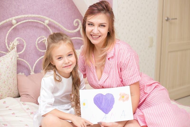 De kinddochter wenst mamma geluk en geeft haar een prentbriefkaar stock afbeeldingen