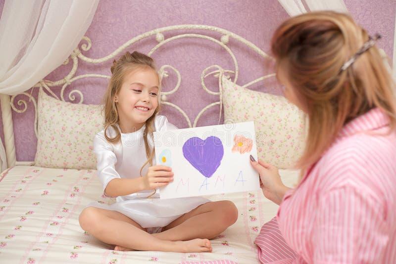 De kinddochter wenst mamma geluk en geeft haar een prentbriefkaar stock afbeelding