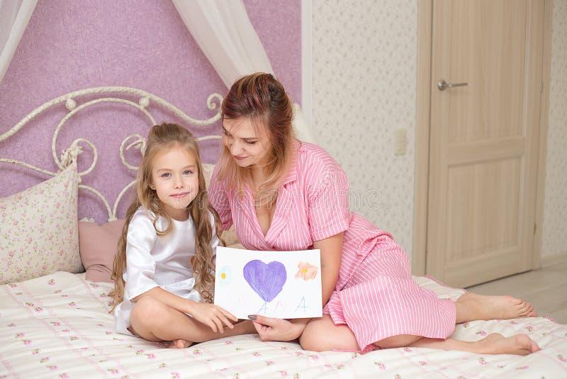 De kinddochter wenst mamma geluk en geeft haar een prentbriefkaar royalty-vrije stock afbeelding