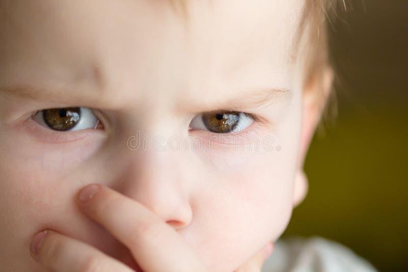 De kinderachtige vrees op het gezicht, bang gemaakt kind, recht close-up kijkt met een ernstig gezicht stock afbeelding