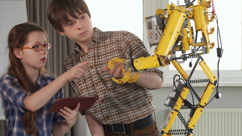 De kinderen controleren de stuk speelgoed robot stock afbeeldingen