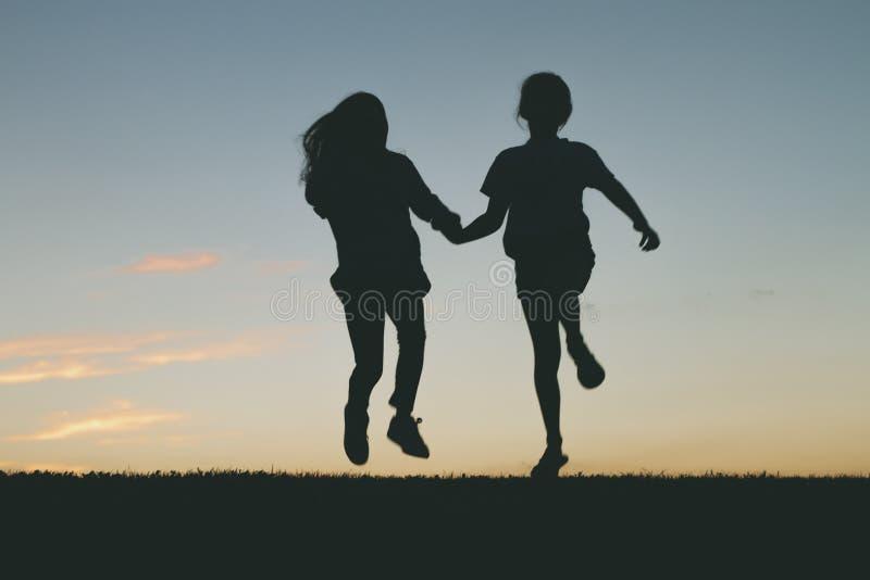 De kinderen die bij zonsondergang springen silhouetteren royalty-vrije stock afbeeldingen