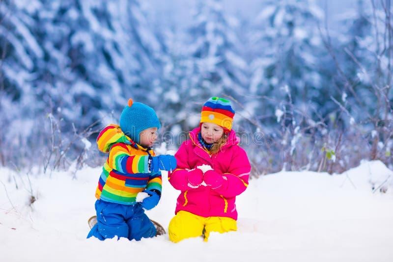De kinderen die in de sneeuwwinter spelen parkeren stock afbeelding