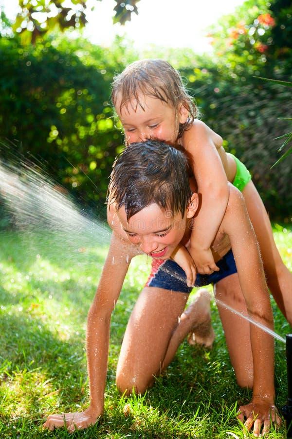 De kinderen die in de zomer spelen tuinieren royalty-vrije stock fotografie
