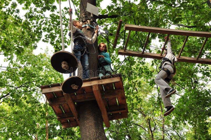 De kinderen die in een het beklimmen avonturenactiviteit genieten van parkeren stock afbeeldingen
