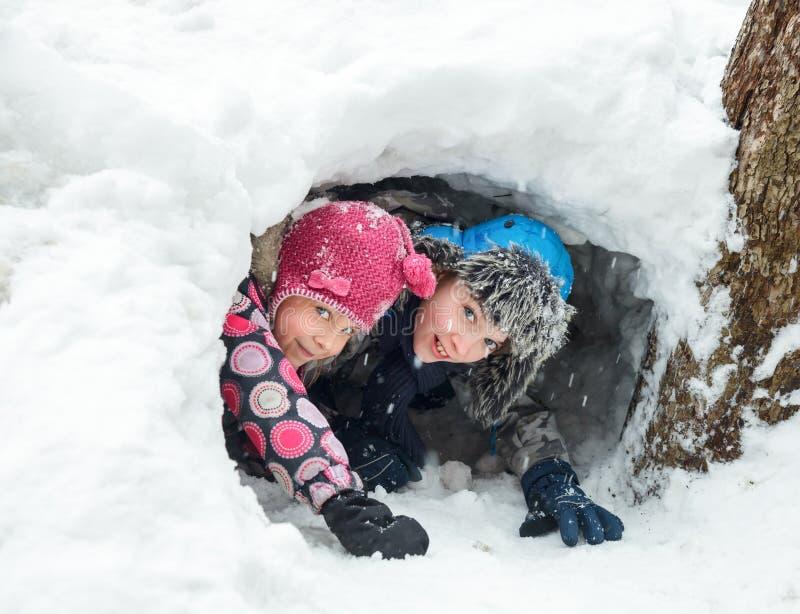 De kinderen die in een sneeuw spelen graven een tunnel stock fotografie