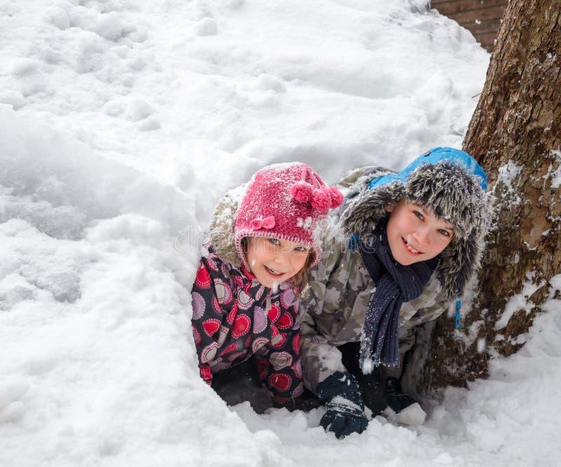 De kinderen die in een sneeuw spelen hollen uit royalty-vrije stock fotografie