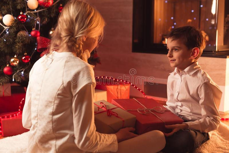De kinderen die Kerstmis uitpakken stelt voor stock fotografie