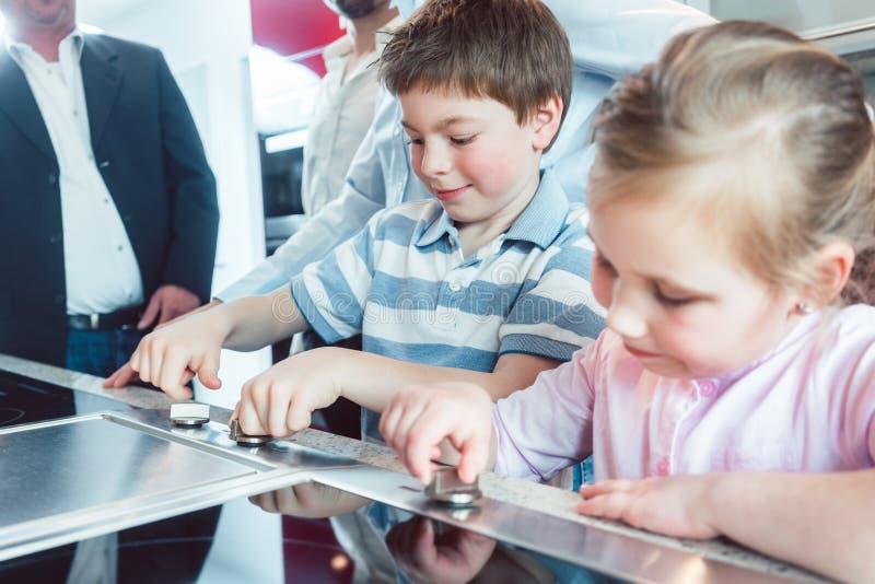 De kinderen die de nieuwe keuken controleren hun ouders staan op het punt te kopen royalty-vrije stock foto's