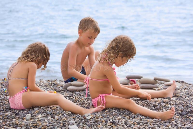 De kinderen die op steenachtig strand zitten, creërt piramide royalty-vrije stock afbeeldingen