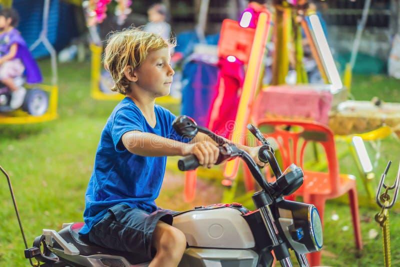 De kinderen die op Vrolijk gaan gaan rond, jonge geitjesspel op carrousel in de zomer stock foto