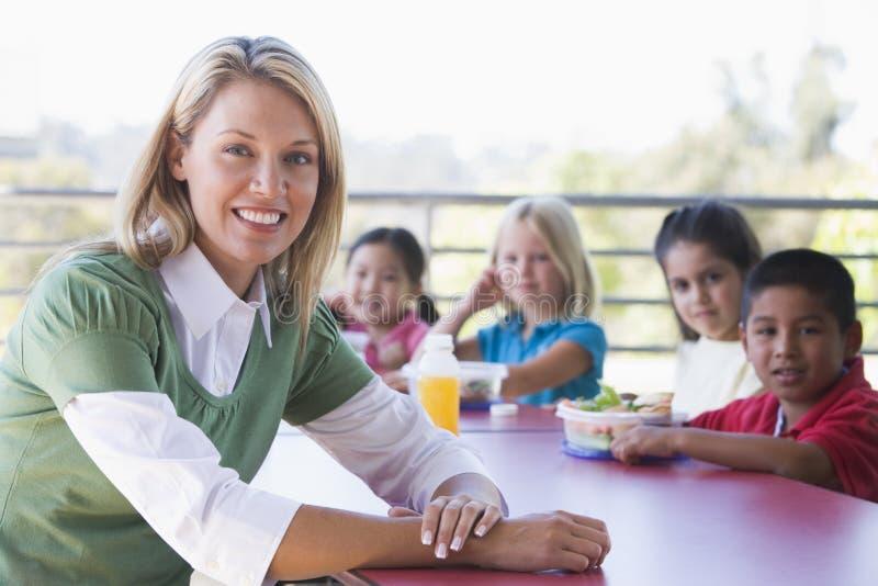 De kinderen die van de kleuterschool lunch eten stock afbeeldingen