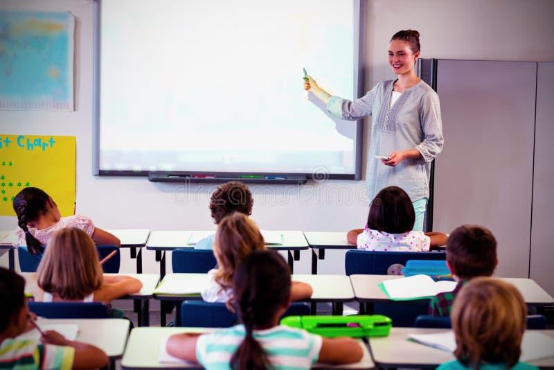 De kinderen die van het leraarsonderwijs projector met behulp van stock afbeelding