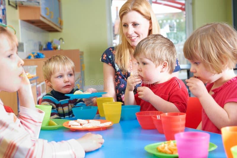 De Kinderen die van leraarswith pre school Gezonde Snacks eten in Breakt royalty-vrije stock fotografie