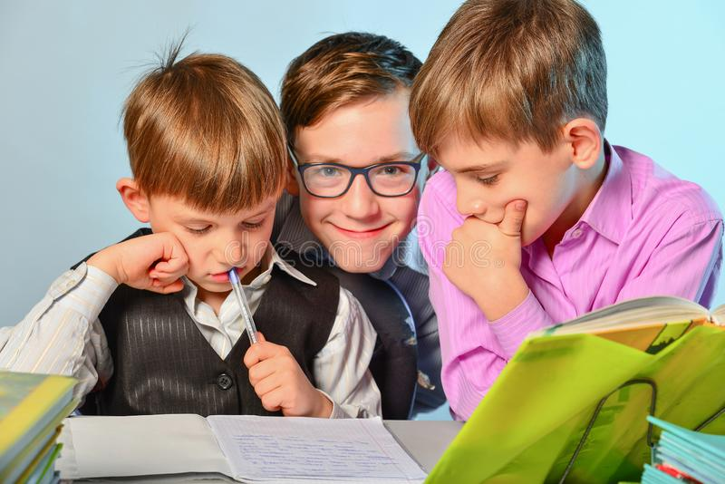 De kinderen doen hun thuiswerk, lossen problemen op en worden klaar voor school stock afbeeldingen