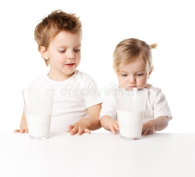 De kinderen drinken melk, op witte achtergrond wordt geïsoleerdi die stock afbeeldingen