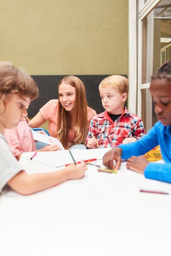 De kinderen en de opvoeder schilderen in tekeningsklasse royalty-vrije stock foto's
