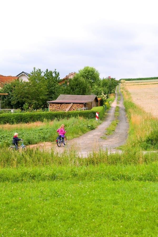 De kinderen gaan op de gebiedsweg stock fotografie