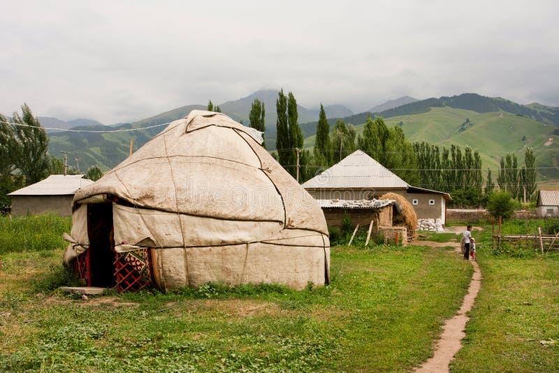 De kinderen gaan voorbij het Centrale Aziatische huis van het yurtdorp weg stock afbeeldingen