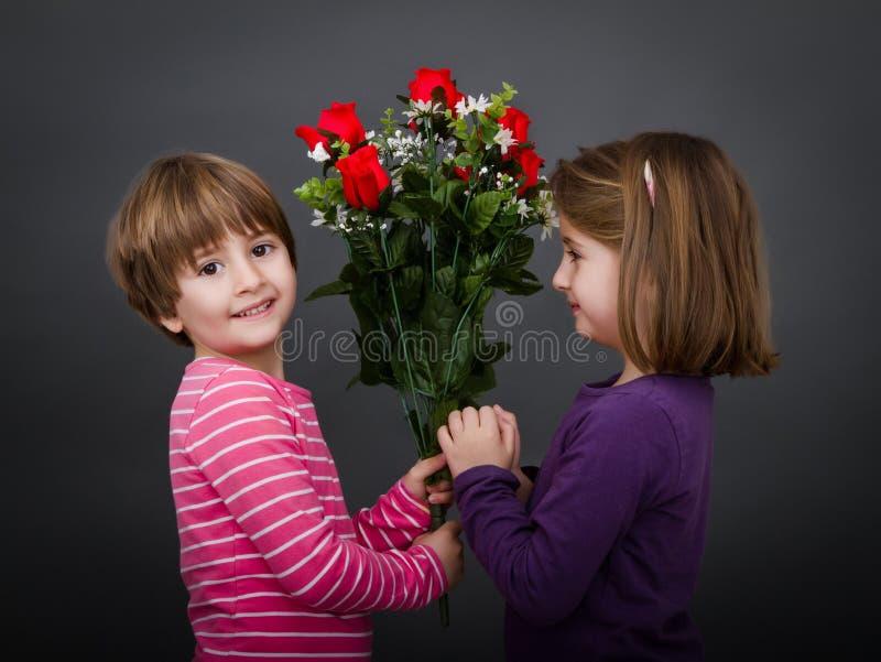 De kinderen geeft rode rozen royalty-vrije stock foto