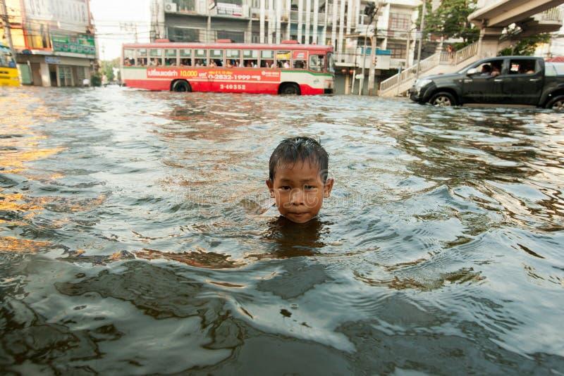 De kinderen genieten van overstroomde te baden straten