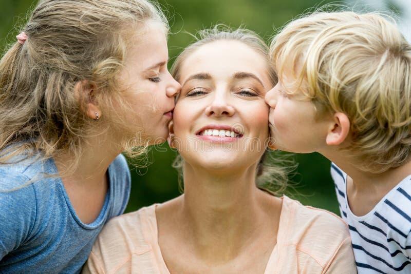 De kinderen geven moeder een kus royalty-vrije stock afbeeldingen