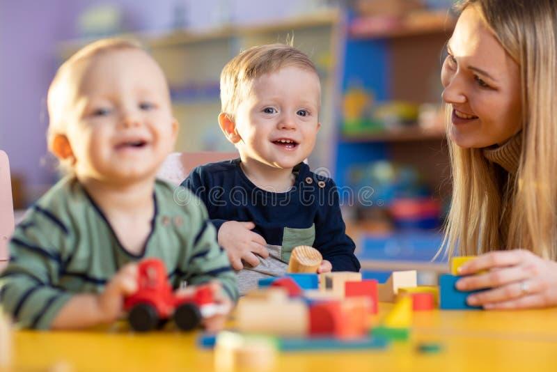 De kinderen groeperen het spelen met leraar in de speelkamer van het opvangcentrum stock foto's