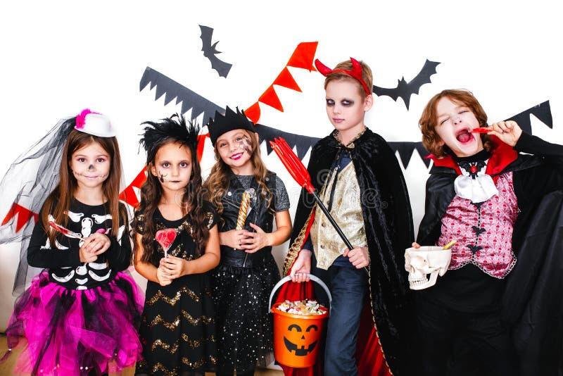 De kinderen in Halloween-kostuums tonen grappige gezichten royalty-vrije stock afbeelding