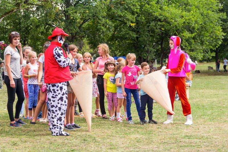 De kinderen hebben pret en spelen met de animators in grappige kostuums royalty-vrije stock foto