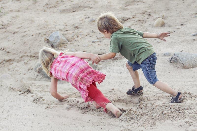 De kinderen helpen elkaar Hulpconcept openlucht stock foto