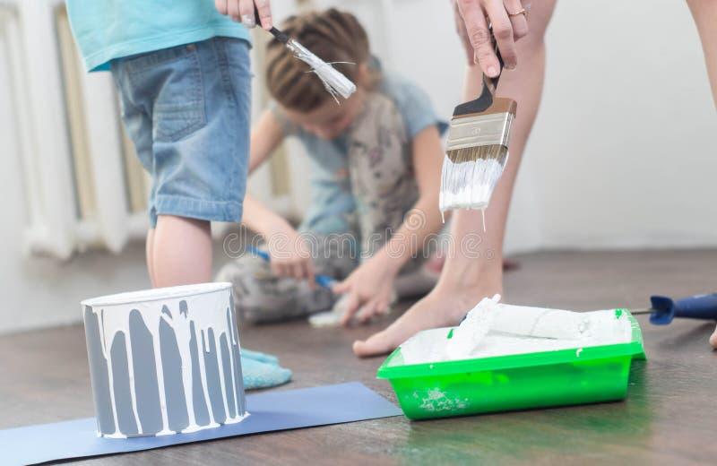 De kinderen helpen in reparaties: een jongen en een meisje dompelen borstels en een rol in witte verf onder stock fotografie