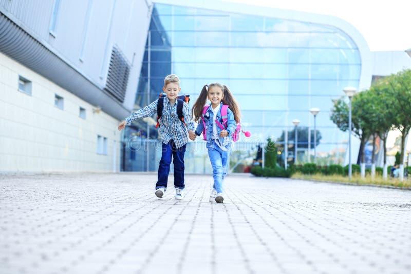 De kinderen houden handen en looppas Schoolkinderen met rugzakken Het concept kinderjaren, familie, onderwijs stock fotografie