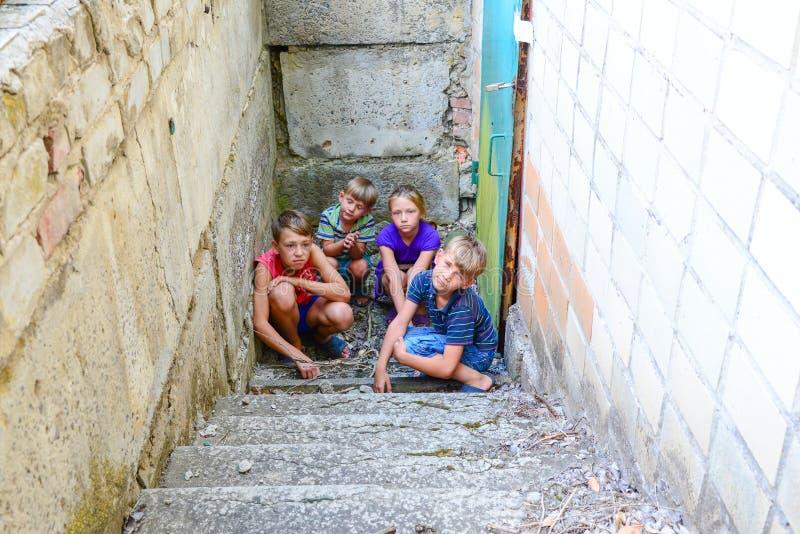 De kinderen in de kelderverdieping, drie jongens en een meisje dichtbij de ijzerdeur verbergen op de stappen van de buitenwereld  royalty-vrije stock foto's