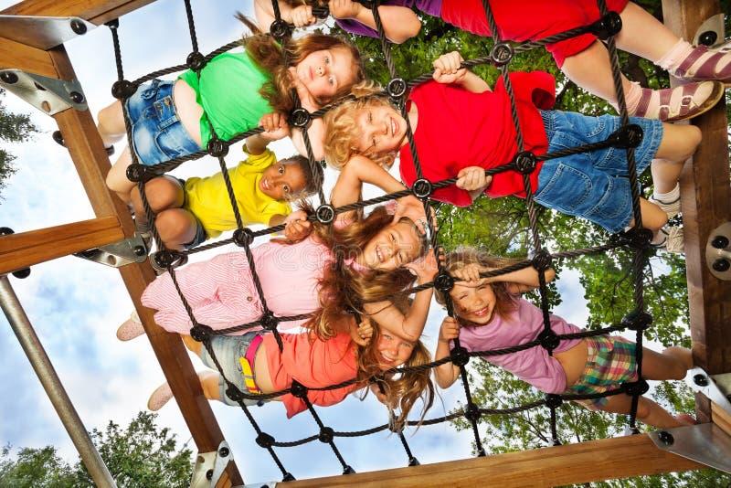 De kinderen kijken hoewel gridlines van speelplaats stock afbeeldingen