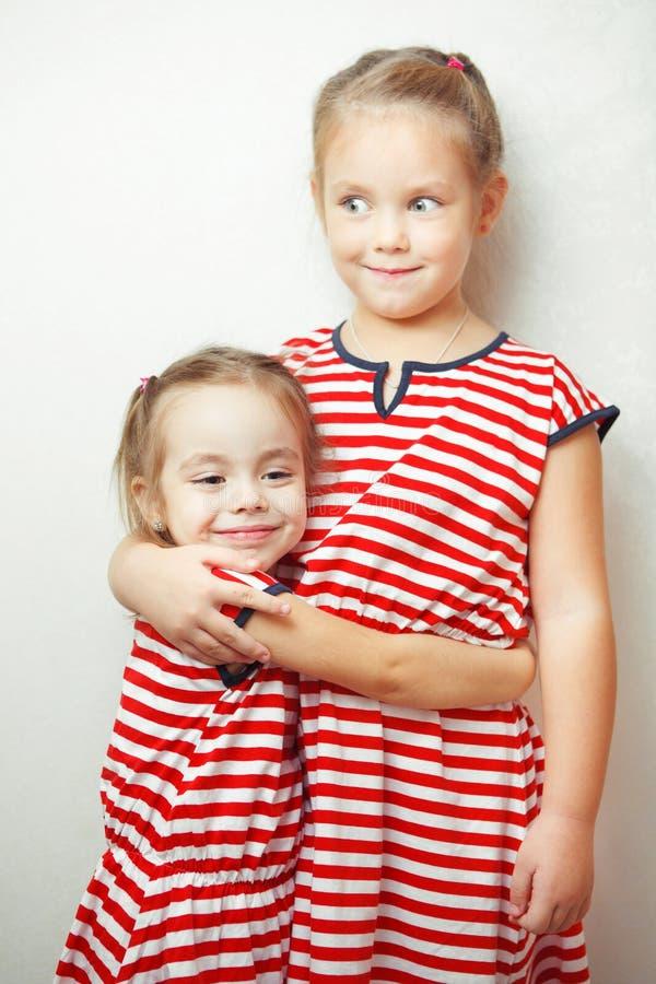De kinderen koesteren elkaar en glimlachen, gelukkige jonge geitjes royalty-vrije stock foto