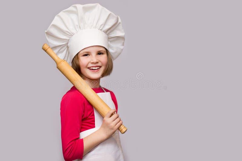 De kinderen koken Het gelukkige die meisje in eenvormige chef-kok houdt deegrol op witte achtergrond wordt geïsoleerd stock afbeeldingen