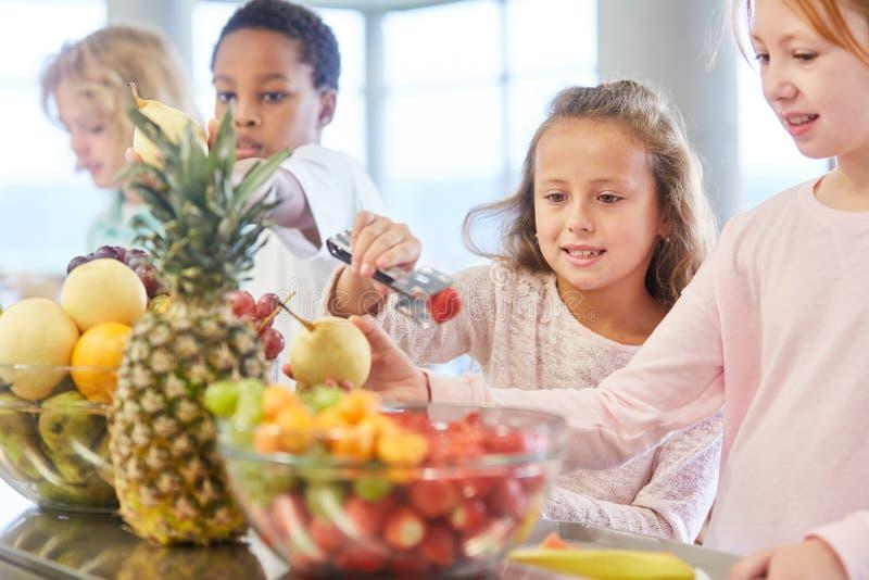 De kinderen krijgen fruit bij het buffet royalty-vrije stock afbeeldingen