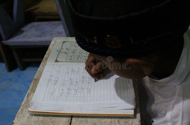 de kinderen leren om al quran in TPA te lezen stock foto