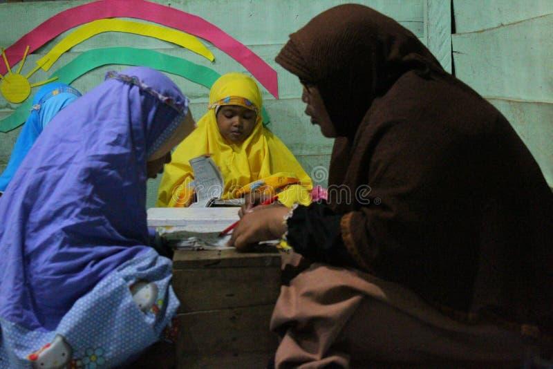 de kinderen leren om al quran in TPA te lezen stock afbeeldingen