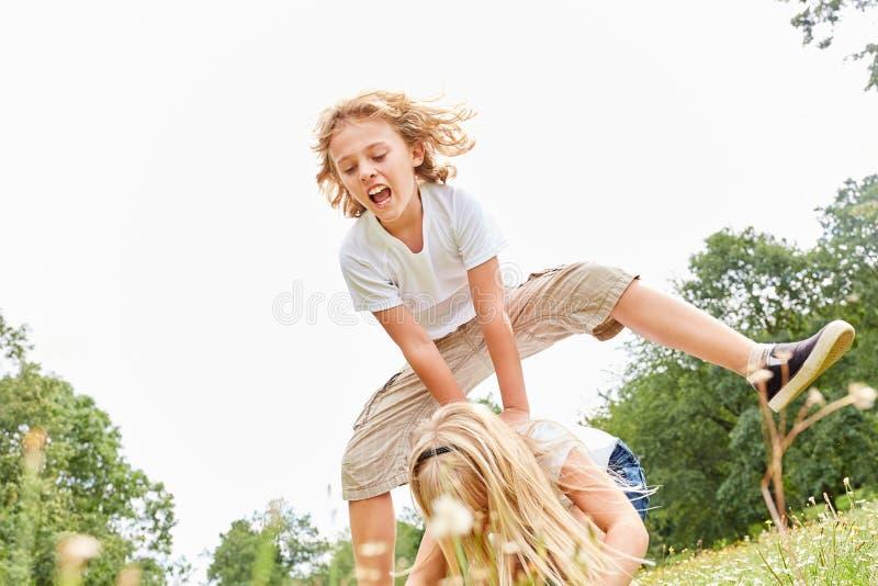 De kinderen maken leapfrog in de zomer stock foto's