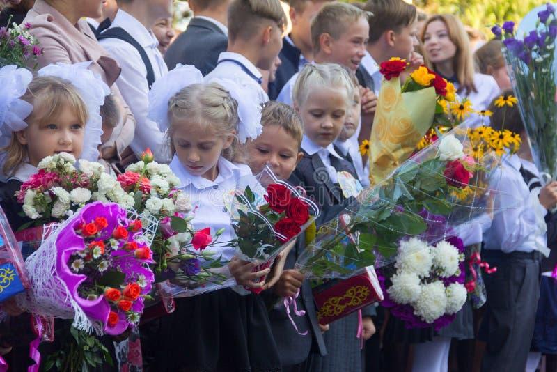 De kinderen met boeketten van bloemen schreven in de eerste rang met middelbare schoolstudenten op school de plechtige heerser in royalty-vrije stock afbeelding