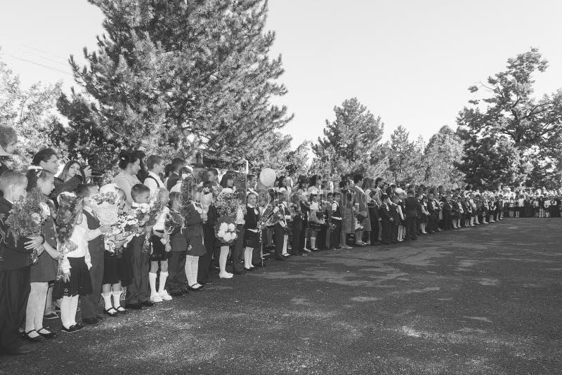 De kinderen met boeketten van bloemen schreven in de eerste rang in school met leraren en leerlingen op een plechtige heerser op  stock foto's