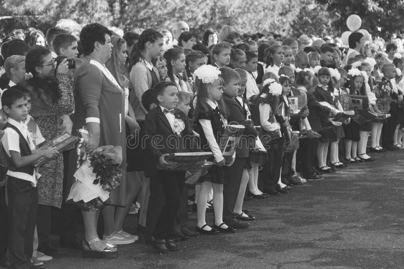De kinderen met boeketten van bloemen schreven in de eerste rang in school met leraren en leerlingen op een plechtige heerser op  royalty-vrije stock afbeeldingen