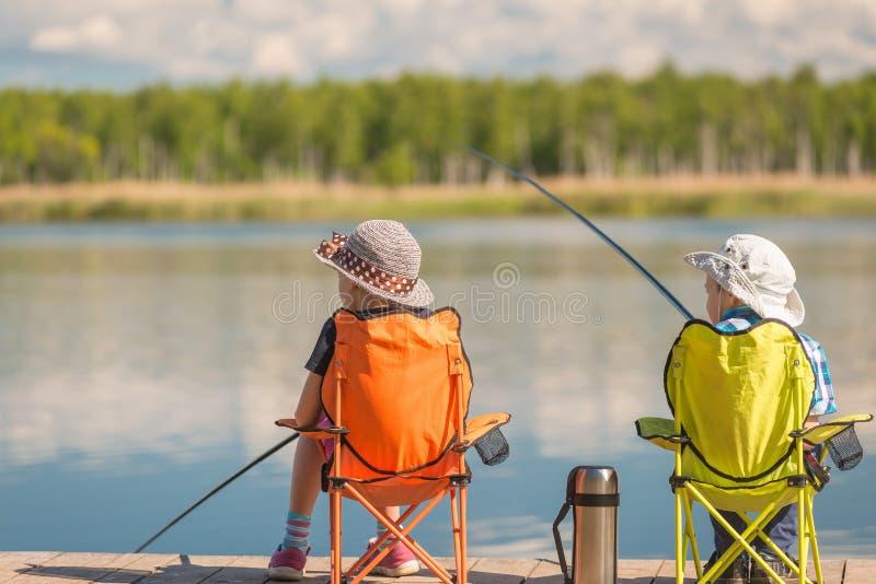 De kinderen met hengels zitten op een houten pijler en een vis stock afbeelding