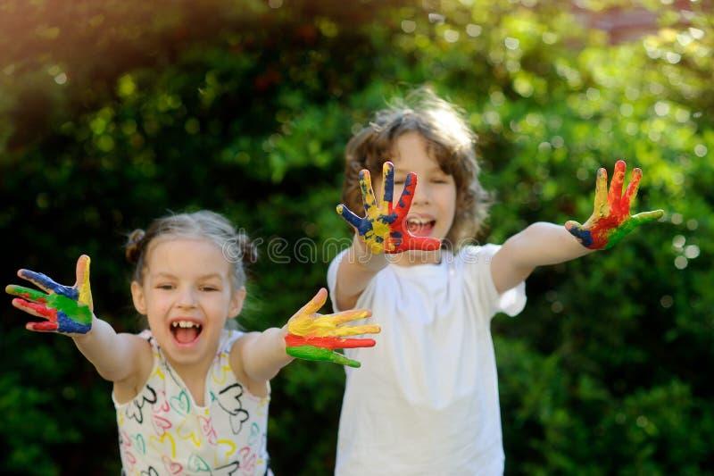 De kinderen met verf worden bevuild en tonen vuile handen die royalty-vrije stock afbeelding