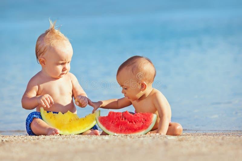 De kinderen na het zwemmen hebben pret en eten vruchten op strand stock afbeelding