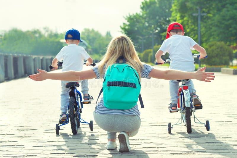 De kinderen nemen aan competities deel berijdend een fiets Familievakantie op de promenade stock afbeelding
