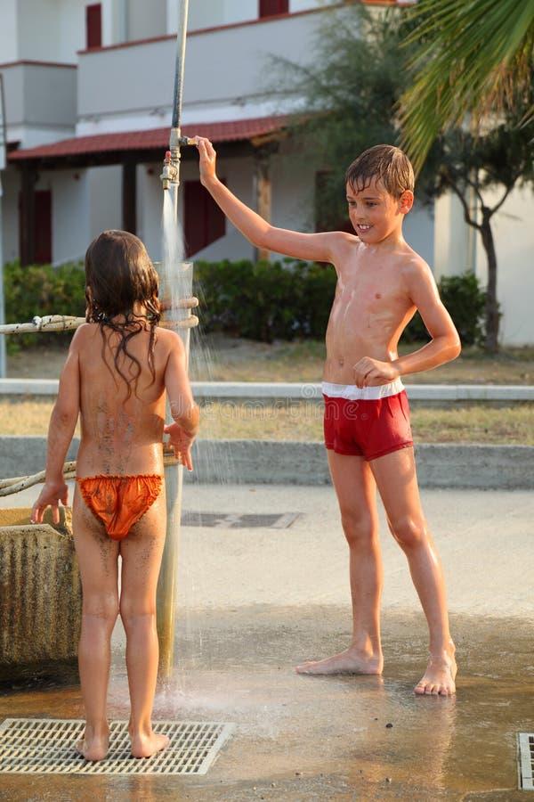De kinderen nemen openluchtdouche na zwemmen royalty-vrije stock fotografie
